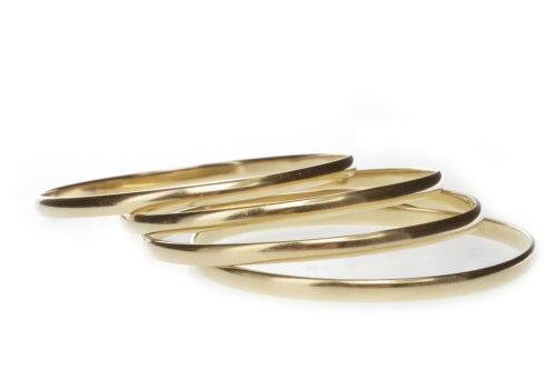 Lot 519-FOUR GOLD BANGLES each of circular form, three...
