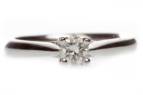 Lot 633 - PLATINUM DIAMOND SOLITAIRE RING with a four...