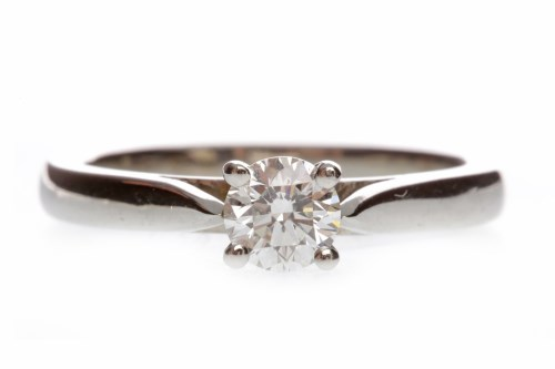 Lot 638 - PLATINUM DIAMOND SOLITAIRE RING with a four...