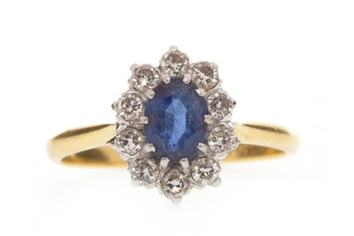 Lot 584 - BLUE GEM SET AND DIAMOND RING set with an oval...