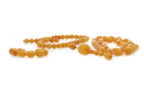 Lot 11-TWO AMBER BEAD NECKLACES ALONG WITH A BRACELET AND A HAT PIN