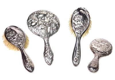 Lot 922 - AN EARLY 20TH CENTURY SILVER BACKED DRESSING TABLE SET ALONG WITH A HAND MIRROR