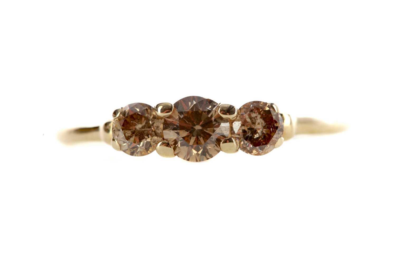 Lot 1382 - A CHAMPAGNE DIAMOND THREE STONE RING