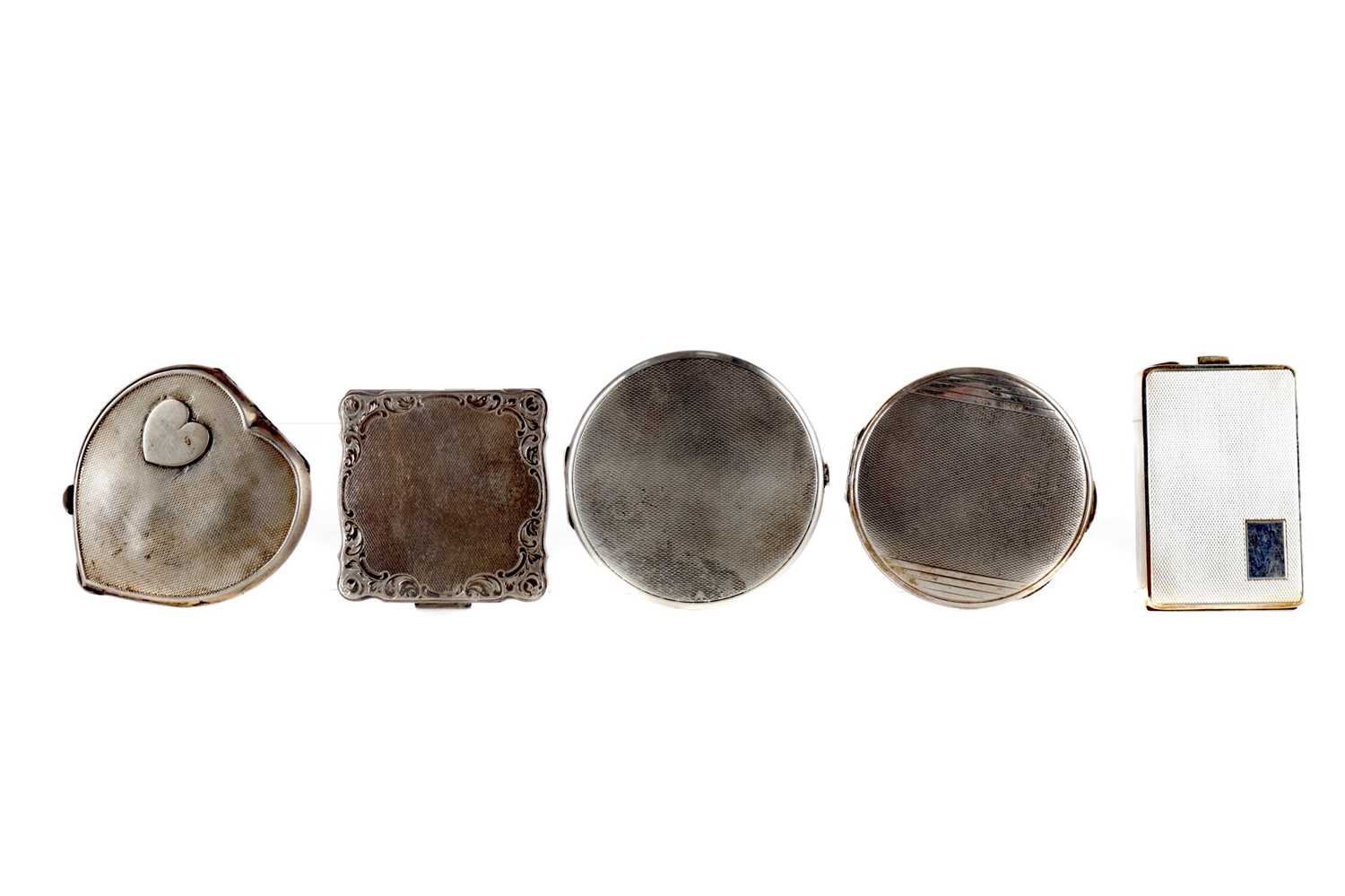 Lot 1710 - A SILVER HEART SHAPED COMPACT AND FOUR OTHER SILVER COMPACTS