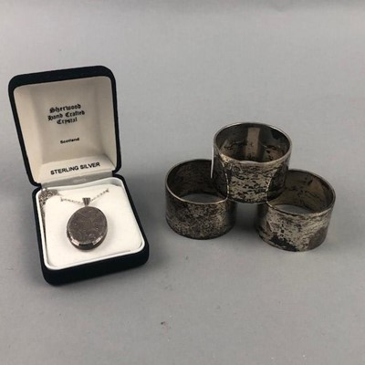 Lot 30 - A LOT OF THREE SILVER CIRCULAR NAPKIN RINGS AND SILVER LOCKET
