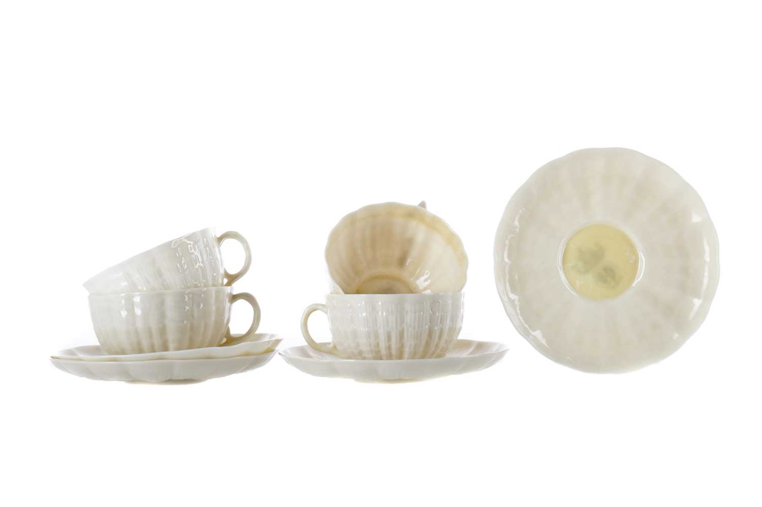 Lot 1100 - A SET OF FOUR BELLEEK BELLEEK TRIDACNA CUPS AND SAUCERS