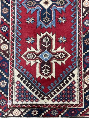 Lot 29 - A MIDDLE EASTERN FRINGED AND BORDERED RUNNER AND A RUG