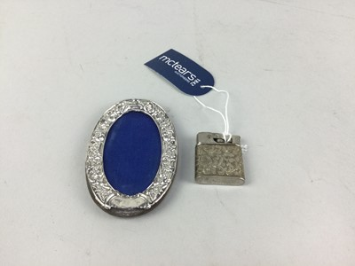 Lot 32 - A SILVER OVAL PHOTOGRAPH FRAME AND A LIGHTER