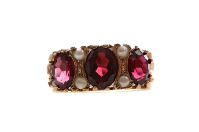 Lot 548 - A RED GEM SET AND SEED PEARL RING