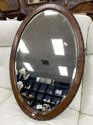 Lot 84 - AN OVAL BEVELLED WALL MIRROR