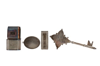 Lot 475 - A GEORGE V SILVER PRESENTATION KEY, ALONG WITH TWO NAPKIN RINGS A MONEY CLIP AND A MEDAL