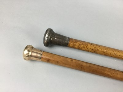 Lot 25 - A GOLD AND A SILVER TOPPED CANE