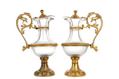 Lot 1729 - A PAIR OF LATE 19TH CENTURY GLASS AND GILTMETAL EWERS
