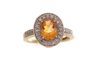 Lot 403 - AN ORANGE GEM SET AND DIAMOND RING