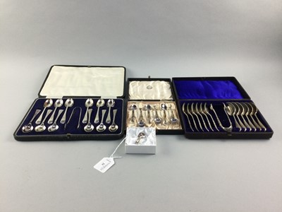 Lot 21 - A SILVER NAPKIN HOLDER, ALONG WITH THREE CASED FLATWARE SETS