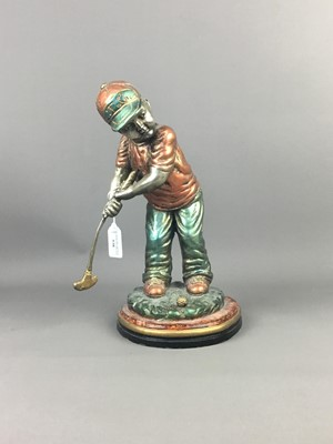 Lot A POLYCHROME CAST METAL FIGURE OF A YOUNG GOLFER