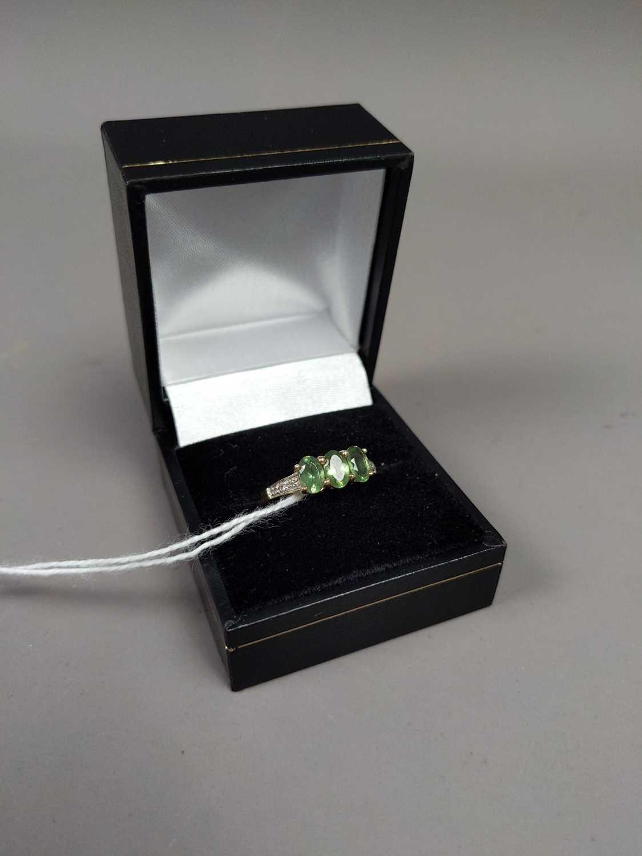 Lot 30 - A DIAMOND AND PERIDOT DRESS RING
