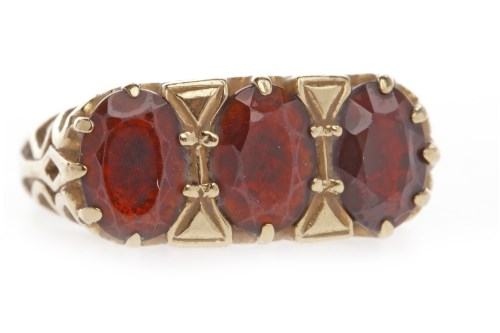 Lot 567-NINE CARAT GOLD GARNET THREE STONE RING set with...